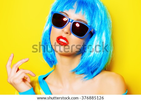 Bright glamorous girl in vivid clothes and a wig alluring over yellow background. Beauty, fashion. Cosmetics, hairtsyle. Optics, eyewear. - stock photo