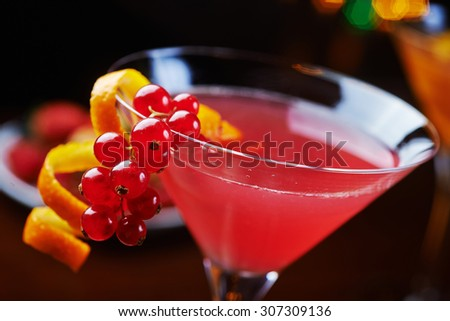bright glass of delicious alcoholic martini cocktail or lemonade with ice and currant on a table in a bar or restaurant with decor and beautiful bokeh in the background. soft focus. - stock photo