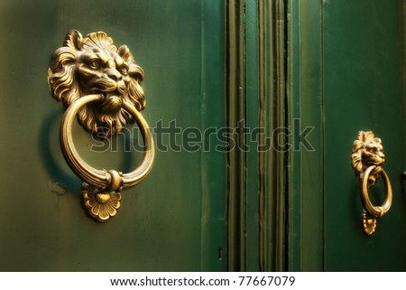 Bright gold lion doorknockers on a pair of old green doors - stock photo
