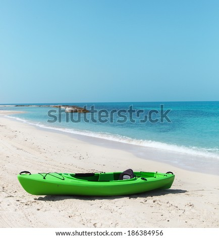 Bright green kayak on the beach - stock photo