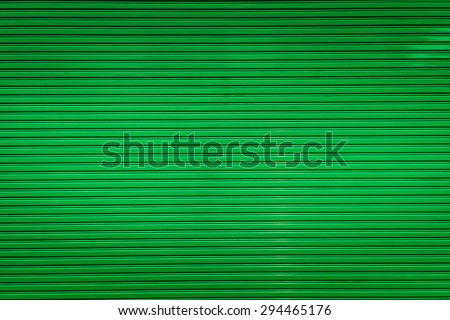 Bright green metal sliding door with key hole, taken on a cloudy day. - stock photo