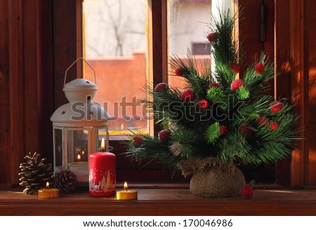 Bright green with fluffy branches a small pine decorated with toys in the form of apples and berries and a beautiful Christmas lantern with burning candle