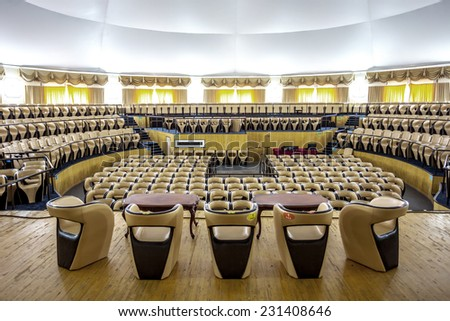 Bright interior of a modern concert hall with a stage and rows of comfortable leather chairs, a stage and acoustic amplification system under natural light, prepared for presentation - stock photo