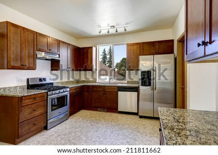 Bright kitchen interior with wooden cabinet, granite tops and steel appliances - stock photo