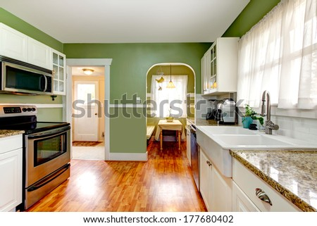 Bright kitchen room with green wall and hardwood floor. Kitchen with white cabinets and steel appliances. Open to dining area - stock photo