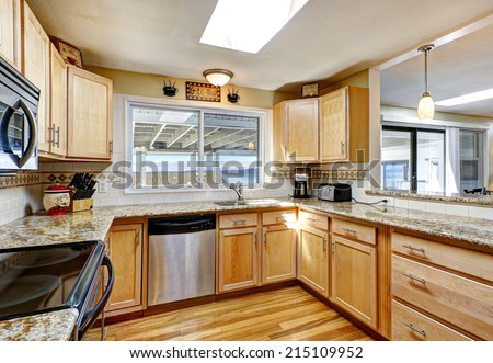 Bright kitchen room with hardwood floor, light tone wooden cabinets with granite tops and steel appliances - stock photo