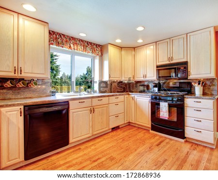Bright kitchen room with light tones furniture and contrast red color walls - stock photo