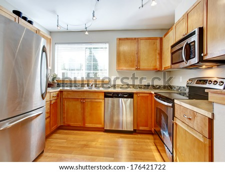 Bright kitchen room with wood cabinets, steel modern appliances, hardwood floor and decorated back splash