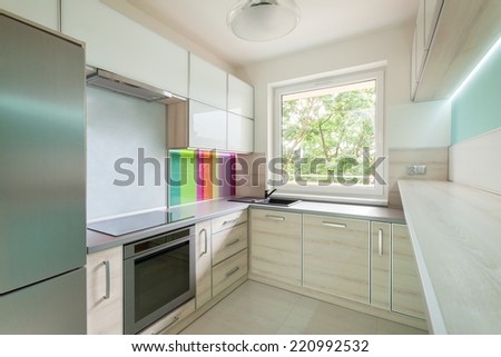 Bright kitchen with colorful decoration on the wall - stock photo