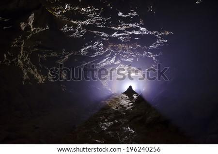 bright light in a dark cave - stock photo