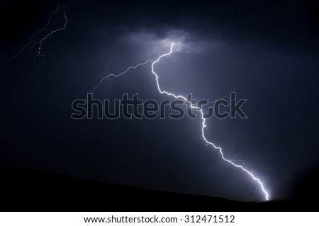 Bright lightning bolt on mountain with radio tower for power and communications - stock photo