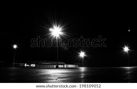 Bright lights in an empty parking lot at night. - stock photo