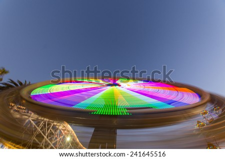 Bright lights on a fairground ride at night - stock photo