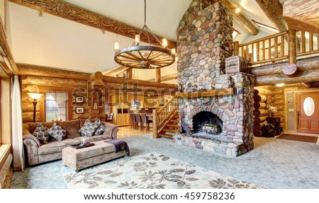 Bright Living room interior in American log cabin house. Rustic chandelier, stone fireplace and high ceiling with wooden beams make room gorgeous. Northwest, USA - stock photo
