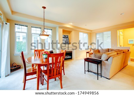 Bright living room with comfortable couch and fireplace including dining area