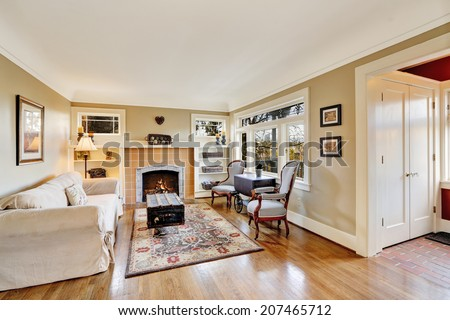 Bright living room with fireplace, antique furniture in old house - stock photo