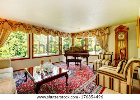 Bright living room with old fashioned couch and chairs, wooden coffee table, grand piano and antique oak grandfather clock - stock photo