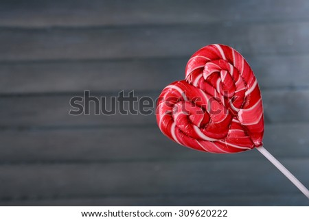 Bright lollipop in shape of heart on wooden background - stock photo