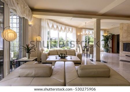 designed living room. Bright  marble designed living room interior surrounded by windows leather sofa and armchairs Luxury Interior Design Living Room Pool Stock Photo 662758963