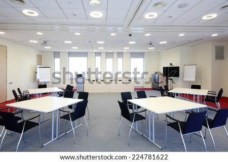 Bright meeting room with four tables and modern equipment - stock photo