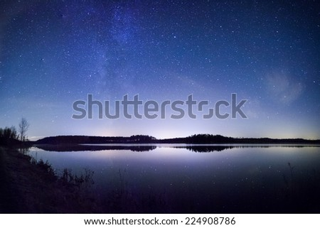 Bright Milky Way over the lake at night in Finland. - stock photo