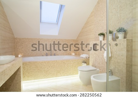 Bright modern exclusive bathroom with inclined wall - stock photo