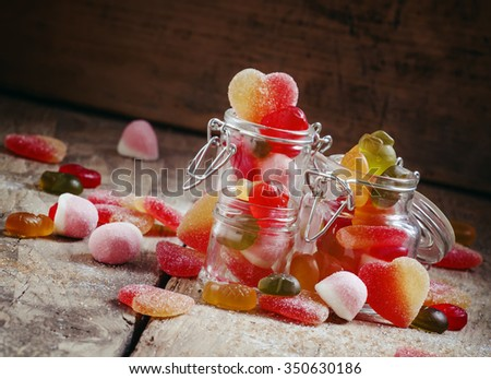 Bright multi-colored jelly candies in glass jar, selective focus - stock photo