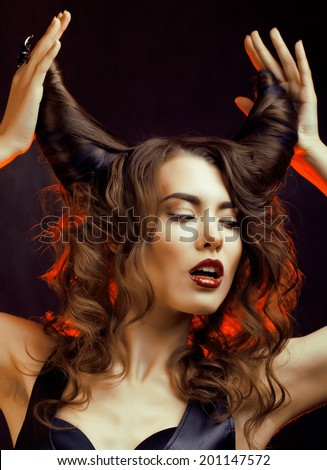 bright mysterious woman with horn hair, halloween celebration - stock photo