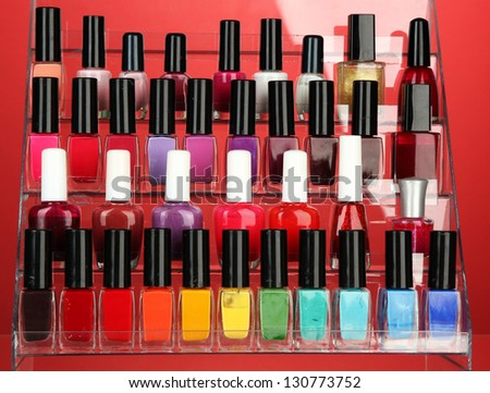 Bright nail polishes on shelf on red background - stock photo