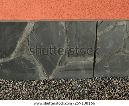 Bright natural colors and materials  in a building exterior. Background with three layers. Colorful wall. Flagstone wall. Gravel next to the wall. European residential housing. - stock photo