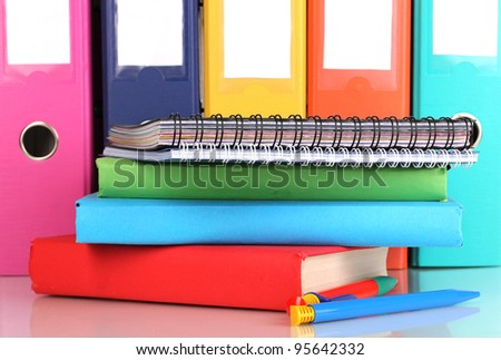 Bright office folders and books with stationery close-up isolated on white
