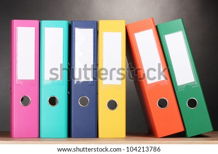 bright office folders on wooden table on grey background - stock photo