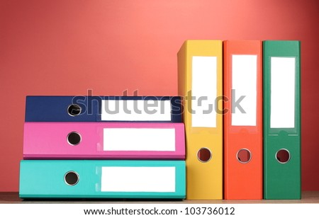 bright office folders on wooden table on red background - stock photo