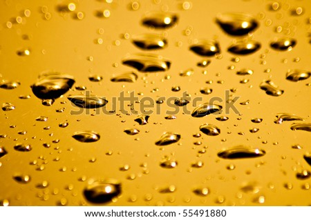 Bright orange and yellow water droplets on the hood of a car - stock photo