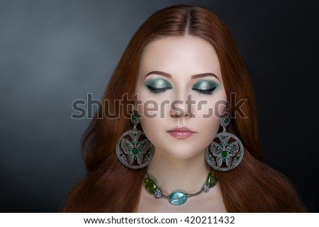 Bright orange brown long straight hair. Oriental beauty girl professional makeup. Portrait of a beautiful girl who wore big silver green accessory. Young gypsy fortune teller predicts fate - stock photo