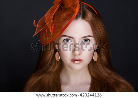 Bright orange brown long straight hair. Oriental beauty girl professional makeup. Portrait of a beautiful woman who wore big red hat accessory. Young gypsy fortune teller predicts fate horoscope - stock photo