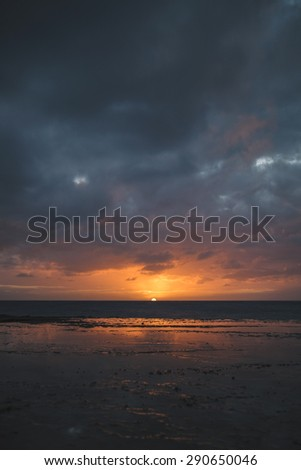 Bright orange glowing of the sun on the horizon moments before it dips beneath the horizon as seen from a rocky coastline. Reflection of the orange glow seen in a puddle in the foreground.  - stock photo