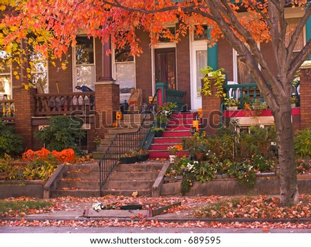 Bright orange leaves hang in front of rowhouse porches in autumn. - stock photo