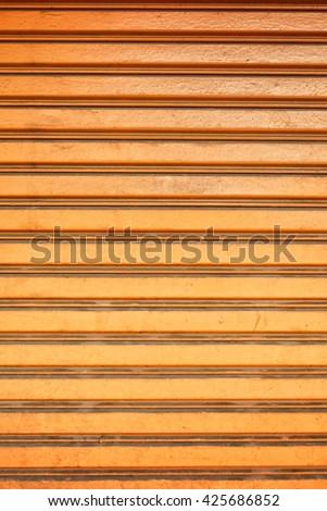 Bright orange roller shutter door - vivid background - stock photo