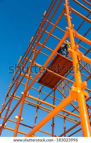 Bright orange scaffolding pipes against a blue sky - stock photo
