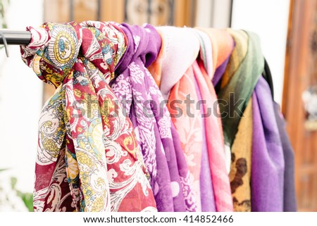 Bright ornamental scarves hanging on metal bar for sale outdoor - stock photo