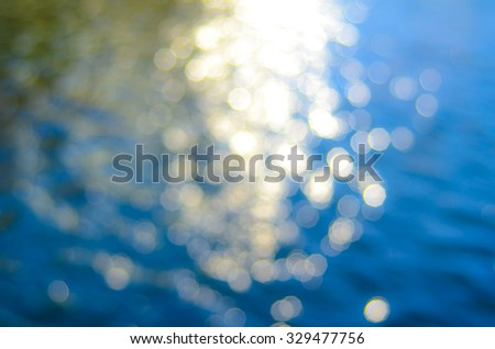 Bright out of focus colorful water and sun reflection at evening true bokeh blurred background. - stock photo