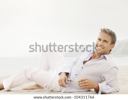 Bright outdoor fashion lifestyle portrait of a great looking young male model with nice happy smile lying down in classic casual clothing - stock photo