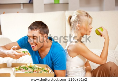 bright picture of couple eating different food (focus on man) - stock photo
