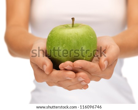 bright picture of female hands with green apple - stock photo