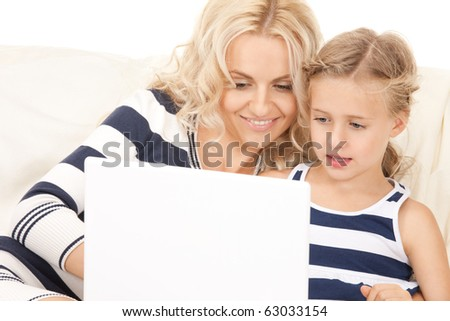 bright picture of happy mother and child with laptop computer - stock photo