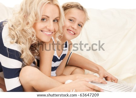 bright picture of happy mother and child with laptop computer (focus on woman) - stock photo