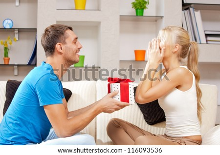 bright picture of happy romantic couple with gift (focus on man) - stock photo