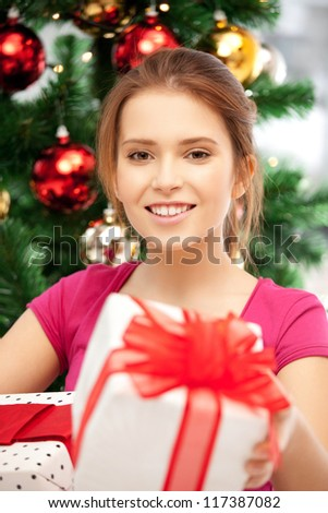 bright picture of happy woman with gift box and christmas tree...... - stock photo
