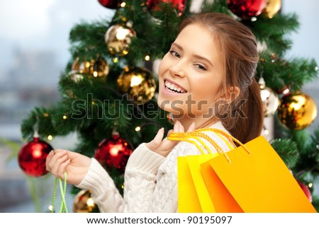 bright picture of happy woman with shopping bags and christmas tree - stock photo